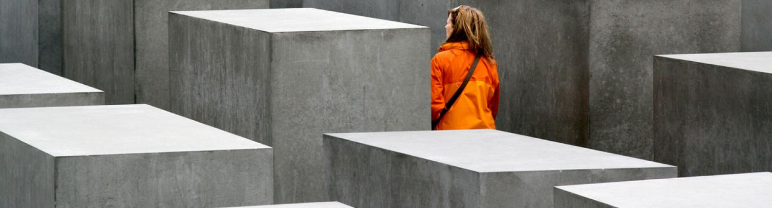 image of woman walking through holocaust memorial